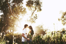 couple hugging outdoors in a field under sunlight