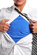 A man pulling his shirt open to reveal a blue shirt beneath.