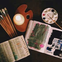 An open Bible with highlighted verses next to artist painting tools.