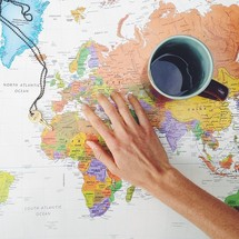 a hand, a key, and a coffee mug on a world map