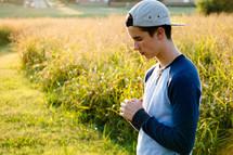 a teenage boy praying outdoors