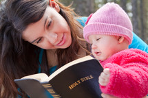 Mother and infant daughter reading the Bible outdoors.