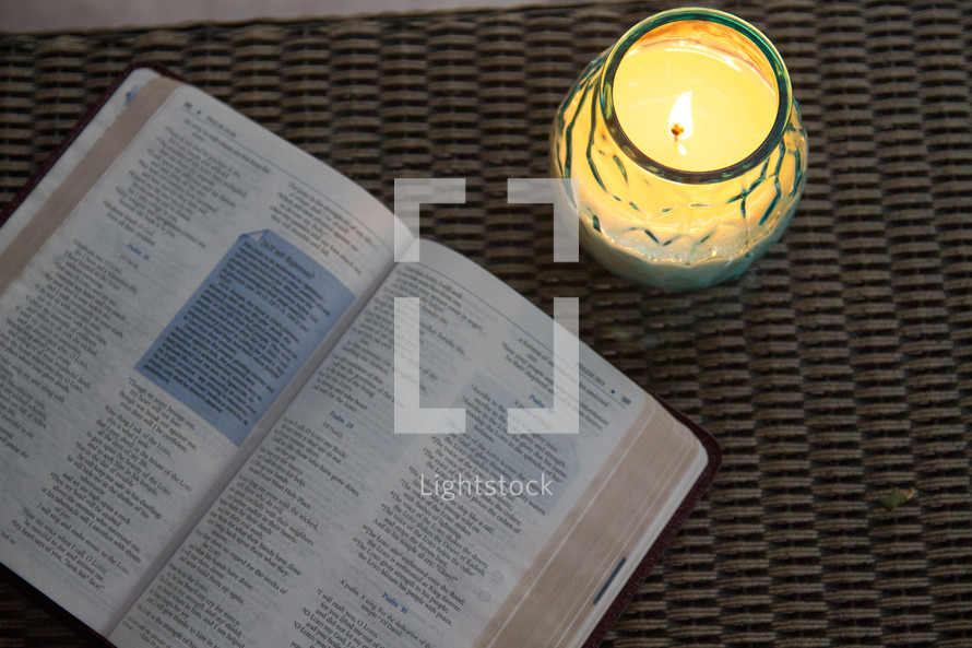 Lit candle and open Bible on a wicker table.