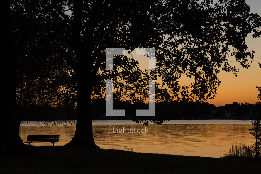 sunset and a park bench near a lake