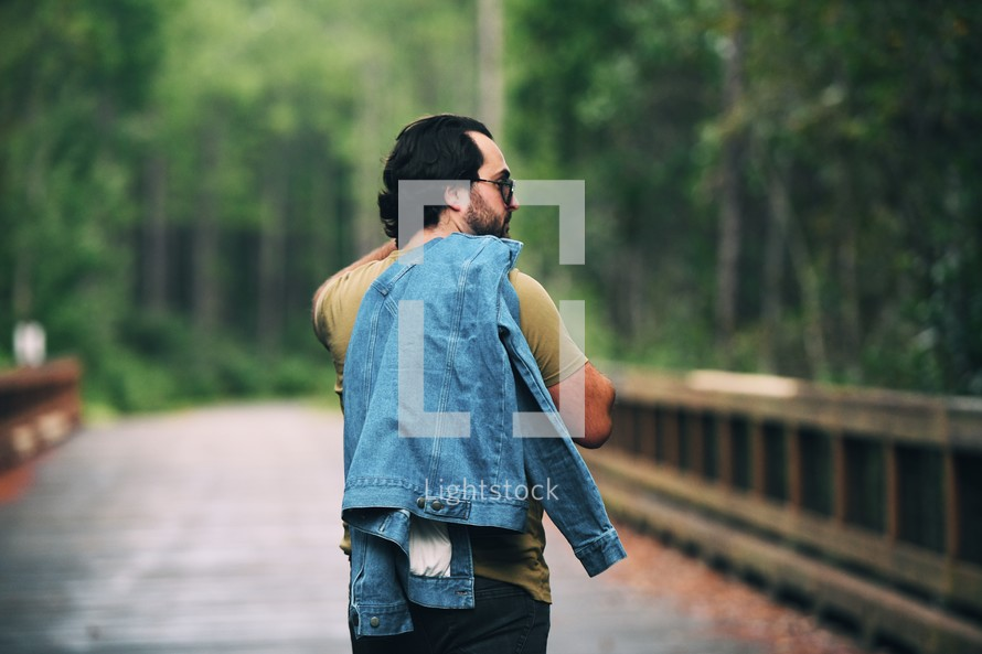 a man walking outdoors with a denim jacket over his shoulders