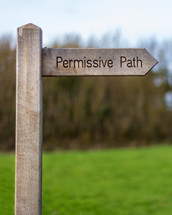 "A wood trail sign points the way of the ""Permissive Path"" with trees and a meadow in the background"