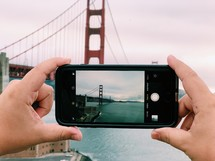a person taking a picture of the Golden Gate bridge with their cellphone