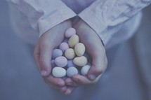 cupped hands holding candy Easter eggs