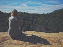 woman sitting at the edge of a cliff looking out