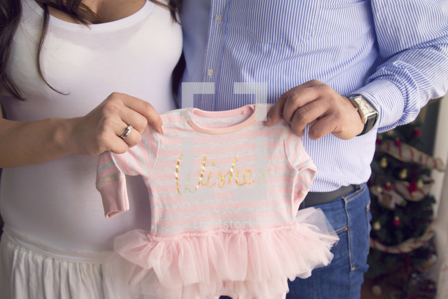 mother and father holding up an infant onesie with a tutu