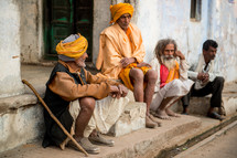 men sitting on the dusty streets of India