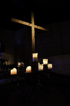 Wooden cross with six lit, white candles at the base.