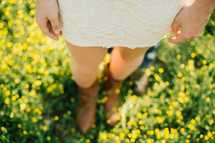 a woman standing in a meadow of yellow spring flowers