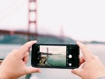 a person taking a picture of a bridge