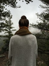 a woman in a sweater with her back to the camera looking out at the foggy valley below