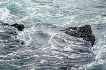Ocean waves covering and surrounding rocks.