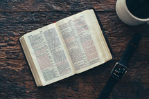 pages of a Bible, smartwatch, and coffee cup