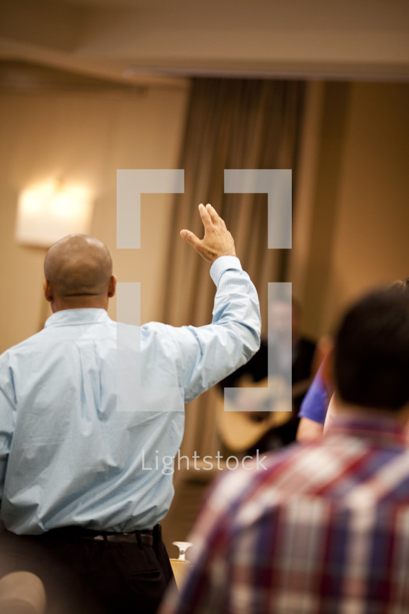 Man in meeting with hands raised