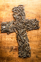 A cross made out of screws and nails on a workbench (portrait)