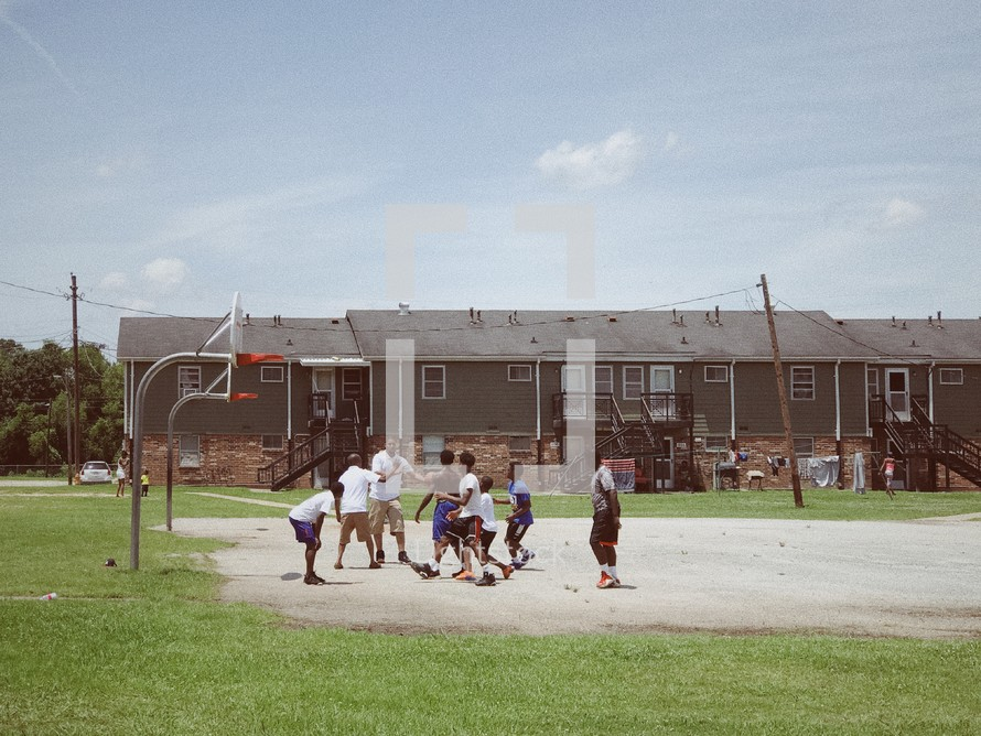 youth playing basketball outdoors