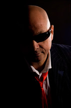 Bald man wearing sunglasses and suit