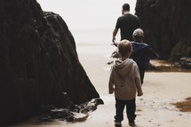 father and sons exploring a beach in fall