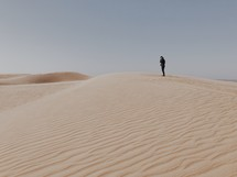 a man standing at the top of sand dunes