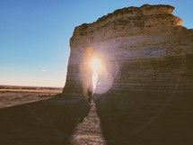 a man walking through a rock formation in a desert at sunset