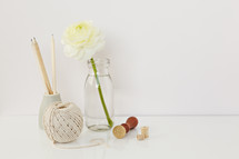 white flower in a clear vase, pencils, yarn, and stamp