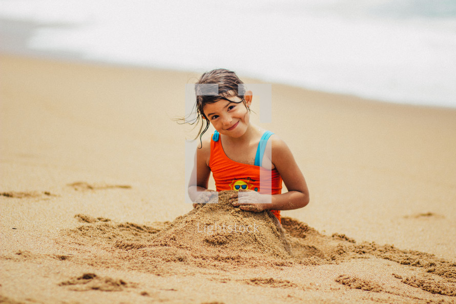 A young girl covering herself with sand on the beach.