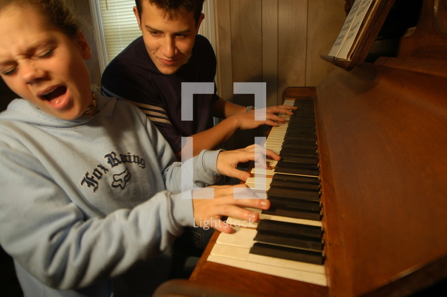 Woman and man playing a jam session duet on an old piano