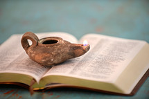 oil lamp on the pages of a Bible