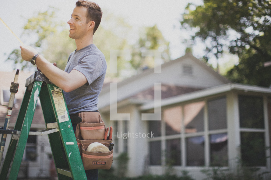 man on a ladder painting