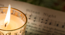 "Lit candle om ""Silent Night"" sheet music."
