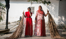 women sweeping in India with palm fronds