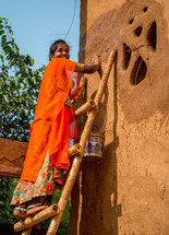 a woman painting a house in India