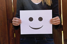 a woman holding a happy face sign