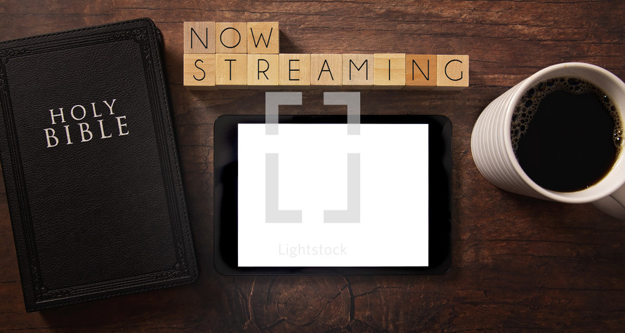 Bible and notebook on a wood background - now streaming