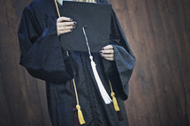 a teen girl holding a graduation cap