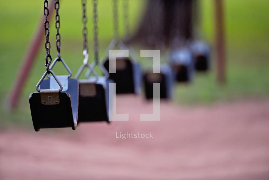 empty swings on a swing set