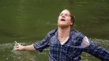 Man dunking himself in lake water.
