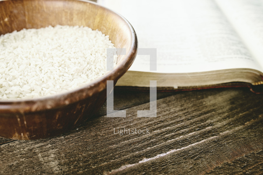 wood bowl of rice and Bible