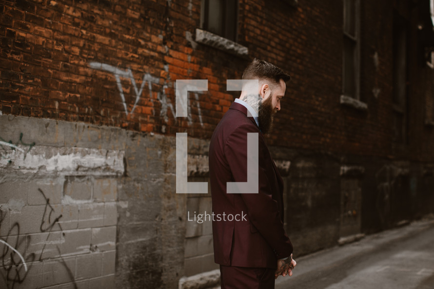 groom standing in an alley in front of a brick wall