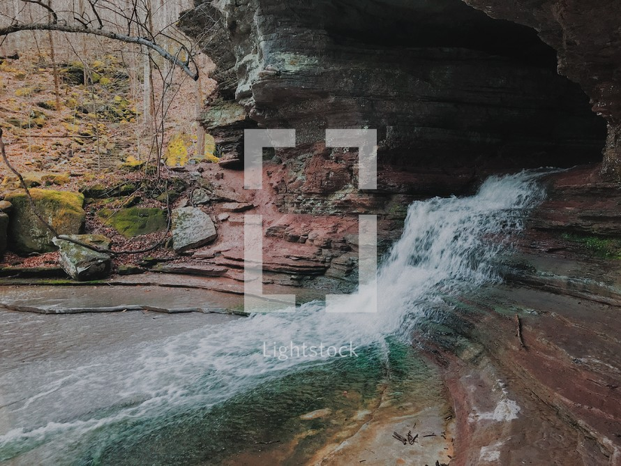 waterfall flowing from the mouth of a cave