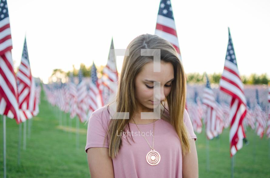 A woman praying near patriotic Valor Flags