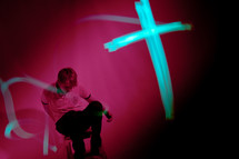 cross in lights in front of a man