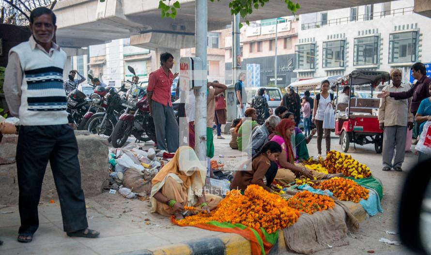women selling flowers on a street corner in Delhi, India