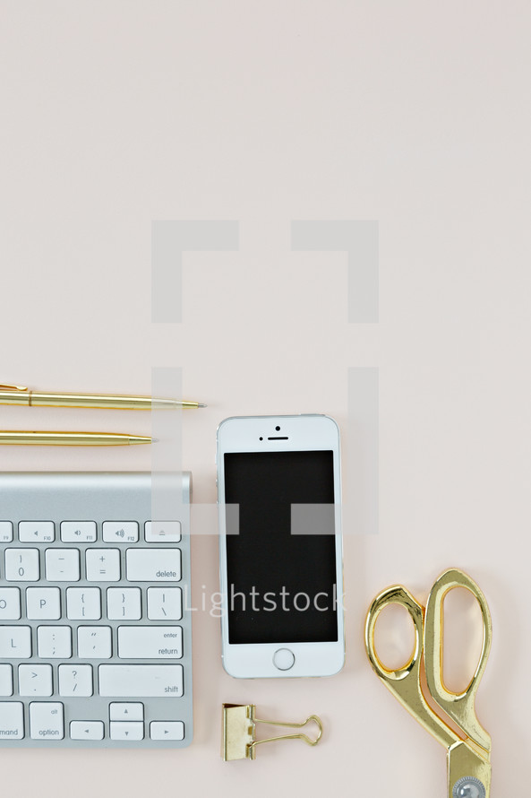 gold scissors, computer keyboard, cellphone, clip, and pens on a desk