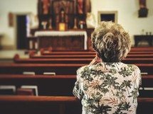 elderly woman praying alone in a church
