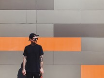 man standing in front of a gray and orange wall